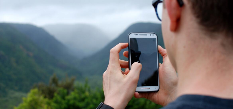 Randonneur avec son smartphone en montagne